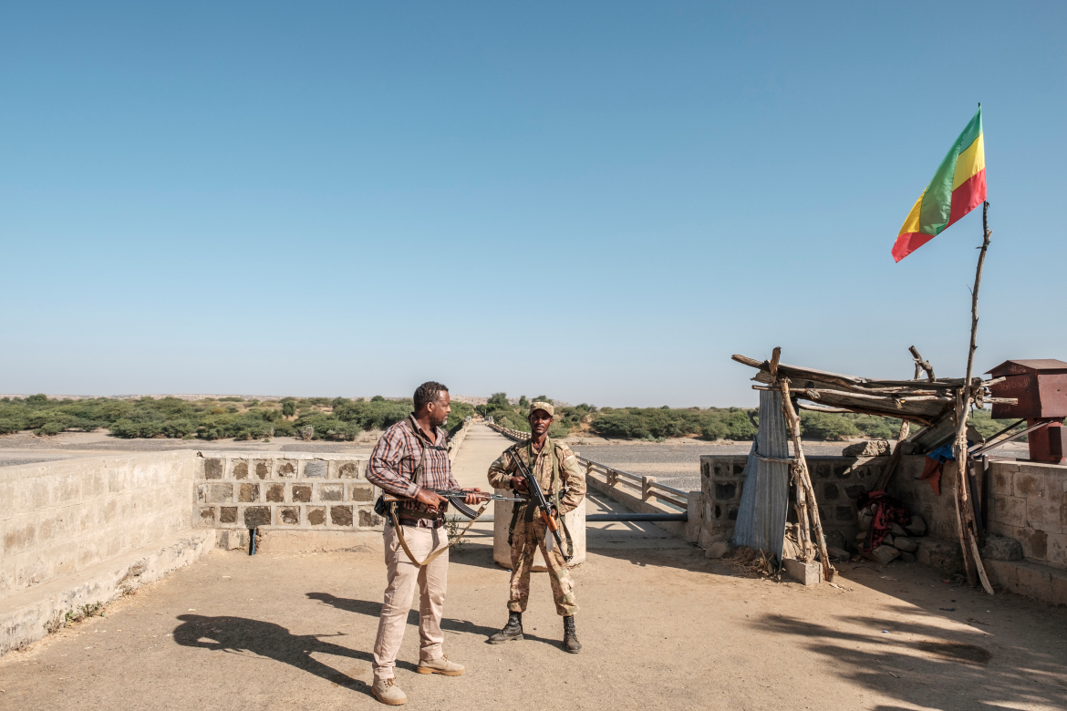 A member of the Amhara Special Forces with a member of the Amhara militia, left, at the border crossing with Eritrea where an Imperial Ethiopian hangs above. [Eduardo Soteras/AFP]