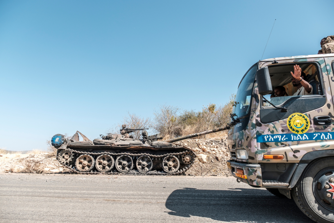 A damaged tank stands abandoned on a road as a truck of the Amhara Special Forces passes by near Humera. [Eduardo Soteras/AFP]