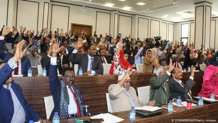 Somali lawmakers raise their hands to confirm the appointment of Prime Minister Mohamed Hussein Roble in 2020